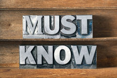 Must know tray. Must know phrase made from metallic letterpress type on wooden tray Royalty Free Stock Images