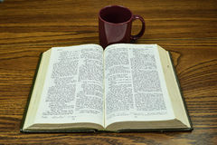 A  must read. A book and cup taken at 125th of a sec. at f11 Royalty Free Stock Image