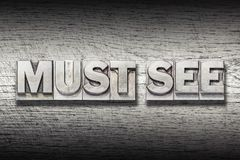 Must see met. Must see phrase made from metallic letterpress on rough wooden texture Royalty Free Stock Photos