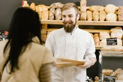 Ο χαρισματικός αρτοποιός με μια γενειάδα και mustache δίνει μια τσάντα εγγράφου του ψωμιού στον πελάτη στο αρτοποιείο στοκ φωτογραφία