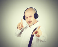 Mustache businessman listening to music on headphones and sings Royalty Free Stock Image