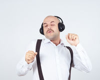 Mustache businessman listening to music on headphones and sings Royalty Free Stock Photo