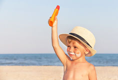 The mustache drawing sunscreen on baby (boy) face. Royalty Free Stock Images