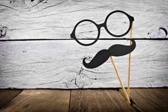 Mustache and glasses on sticks against rustic white wood. Funny mustache and glasses on sticks against a rustic white wood background Royalty Free Stock Images