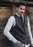 Mustache man modern dressed posing at wooden background Stock Images