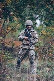 Mustachedmens in militaire eenvormig met een geweer in zijn handen stock foto