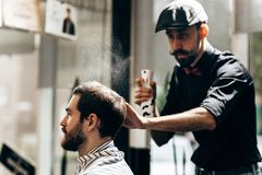 Mustachioed barber dressed in a black shirt and a red bow tie is doing the hair styling to the stylish man sitting in. Mustachioed barber dressed in a black stock image
