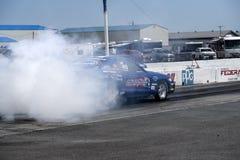 Mustang auf der Bahn, die einen Rauch darstellen lässt Lizenzfreie Stockbilder