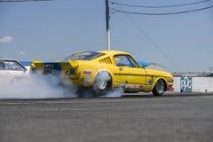 Mustang de vintage sur la voie à la ligne de départ faisant une fumée montrer Image stock