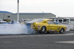Mustang do vintage que faz o fumo mostrar na trilha na linha de partida imagem de stock royalty free