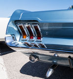 Mustang rear detail. Rear detail with lamp and exhaust of white classic Ford Mustang Royalty Free Stock Photo