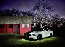 Mustang white turbo light painting with barn. A white Ford Mustang next to a barn, under a starry sky. Taken with light painting technique stock photos