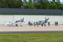 Mustango norteamericano P-51 y fiera de Supermarine aerotransportada cerca del hangar Imagenes de archivo