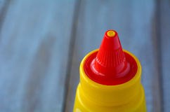 Mustard bottle on a wooden table. Food background and texture with copy space Royalty Free Stock Image