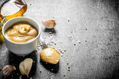 Mustard in a bowl with garlic cloves royalty free stock photo