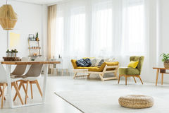 Mustard couch and green chair. Wooden mustard couch and green chair in cozy living room stock photo