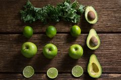 Mustard greens, lemon, avocado and green apple arranged on wooden table stock photos