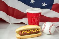 Hot dog with beer and baseball. Mustard on hot dog in bun with overflowing beer in red cup with baseball and American flag background Royalty Free Stock Photos