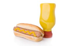 Mustard hotdog and a mustard bottle. Isolated on a white background Royalty Free Stock Image