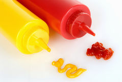 Mustard and Ketchup. Plastic bottles lying on their side with matching ingredients Royalty Free Stock Image