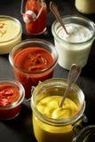 Mustard, ketchup, mayonnaise as dips in jars Royalty Free Stock Image