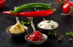 Mustard, ketchup and mayonnaise on black table. Stock Images