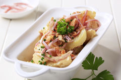 Mustard potato salad. With ham and cracklings royalty free stock images