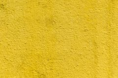 Mustard rough concrete surface, seamless uneven abstract wallpaper. Yellow wal royalty free stock image