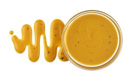 Mustard sauce in bowl isolated on white background. Top view. Honey mustard sauce. Splashes and spilled salad dressing isolated on white background with clipping stock photos