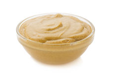 Mustard sauce in bowl on white Royalty Free Stock Photography