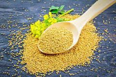 Mustard seeds in wooden spoon with flower on board Stock Photos