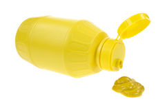 Mustard spilling from bottle. A mustard bottle on it's side with mustard spilling onto a white background Royalty Free Stock Photography