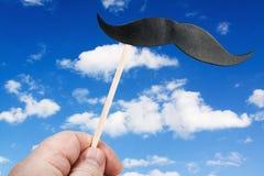 Mustasch på en pinne mot himlen med moln Arkivbild