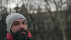 Mustaschhipster i en grå hatt på gatavridningarna hans mustasch arkivfilmer