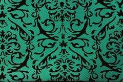 Muster auf einem grünen Stoff Stockfotografie