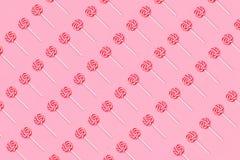 Muster der bunten Lutschersüßigkeit mit Stock auf weichem rosa Hintergrund Flache Lage stockfotos