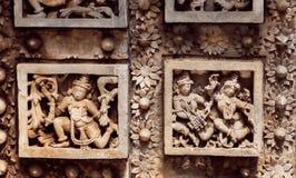 Muster und Tanzenleute auf alten Wänden des hindischen Steintempels mit fantastischen Carvings 12. Jahrhundert, Indien Stockfotos