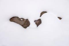 Muster von braunen Pfützen im Schnee Lizenzfreie Stockfotos