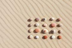 Muster von farbigen Kieseln auf sauberem Sand Zenhintergrund, Harmonie und Meditationskonzept stockbild