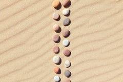 Muster von farbigen Kieseln auf sauberem Sand Zenhintergrund, Harmonie und Meditationskonzept Stockfoto
