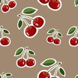 Muster von verschiedenen Größen der roten großen Kirschaufkleber mit Blättern auf braunem Hintergrund Stockfotos