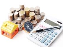 Musterhaus mit Stapelmünzen und Kugelschreiber auf Taschenrechner Lizenzfreie Stockfotos