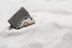 Musterhaus sinkt in den Sand, Konzept des Risikos in den Immobilien Lizenzfreies Stockfoto