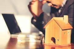 Musterhaus und Geschäftsmann, die Kopfschmerzen mit Finanzproblemen im Innenministerium, ermüdet und Belastung über Immobilien ha lizenzfreie stockbilder