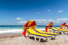 Mustern Sie die anziehenden Sonnenschirme, die auf dem malerischen Mittelmeer Kiesel liegen Stockfoto