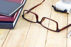 Mustern Sie Gläser und Smartphone und Retrostilkamera auf dem hölzernen Stockfotos