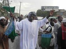 Musulmanes africanos felices que aumentan una bandera Imagen de archivo