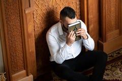 Musulmanes atractivos Guy Kissing The Koran foto de archivo libre de regalías
