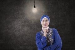 Musulmanes femeninos asiáticos debajo del bulbo encendido en clase Fotografía de archivo