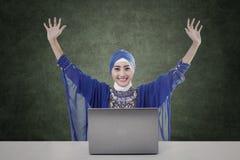 Musulmanes femeninos felices con el ordenador portátil y tablero en blanco Fotos de archivo